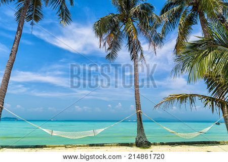 Amazing view of beautiful beach with palm trees hammocks and transparent turquoise water. A great place to relax. Location: Ko Phi Phi Don island Krabi province Thailand Andaman Sea. Artistic picture.