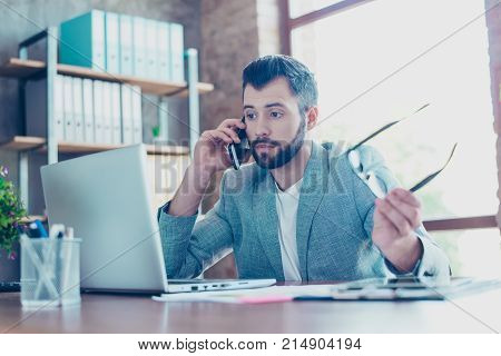 Brunet attractive young banker with bristle in formal jacket talking on the smartphone he is annoyed displeased having conflict with client during telephone conversation sitting at his desktop stock photo