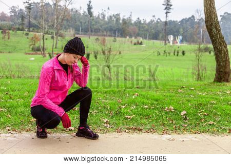 Young woman feeling lightheaded or with headache after train on a cold winter day on the training track of an urban park. Female athlete wearing pink windbreaker, beanie, gloves and running tights stock photo