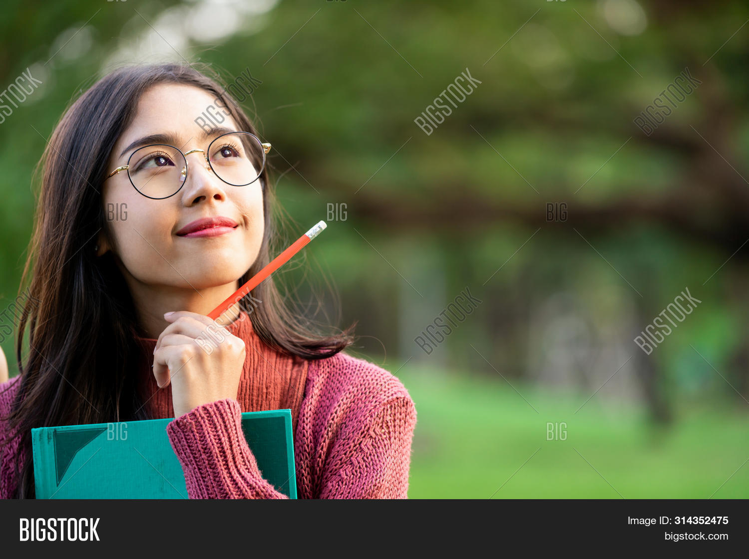 Young Creative Student Girl Thinking Or Planning Future Education While Holding Pencil In Hand. Crea