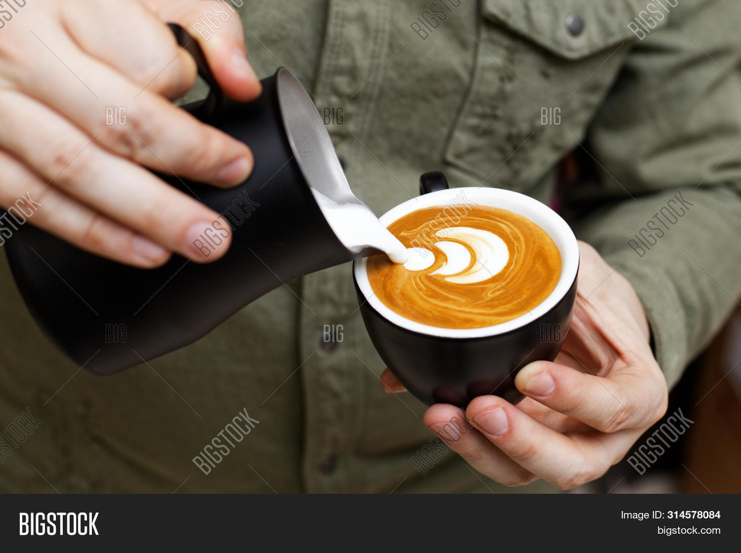 Barista holding a black cup in one hand and a black pitcher in other and pouring milk into a cup of cappuccino to make latte art. Shallow focus.