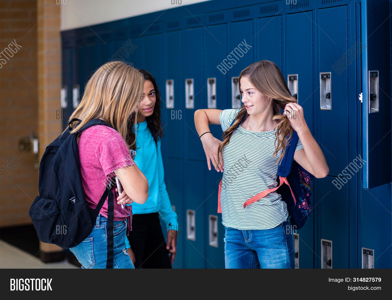 Candid photo of Three Junior High school Students talking together in a school hallway. Diverse Fema