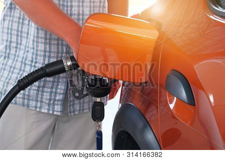 Pumping gasoline fuel in orange car at a gas station. To fill car with fuel in petrol station. Petrol station pump. Sunny. stock photo
