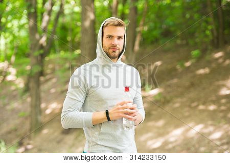 Relaxing after training. refreshing vitamin drink after workout. athletic man with water bottle. Athlete drink water after training. care body hydration. sport and health. man in hood drink water. stock photo
