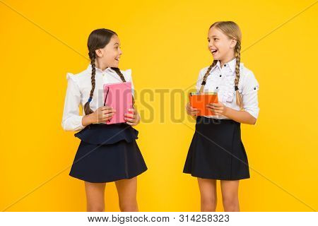 Lets read seriously. Adorable little girls holding library books on yellow background. Cute small children learning to read at primary school. Read and achieve. stock photo