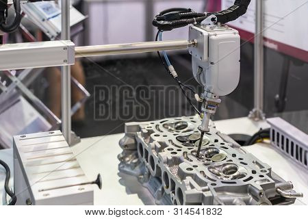 close up suction head and valve shaft during catch remove or assembly in cylinder block engine of vehicle or automobile by automation pneumatic system control stock photo