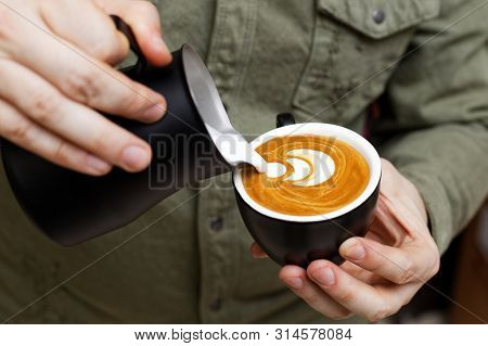 Barista holding a black cup in one hand and a black pitcher in other and pouring milk into a cup of cappuccino to make latte art. Shallow focus. stock photo