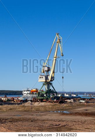 Crane in the port of machinery and forklifts to load and unload pallets on a sunny summer day stock photo