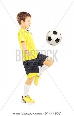 Full length portrait of a child in sportswear joggling with a soccer ball isolated on white background stock photo