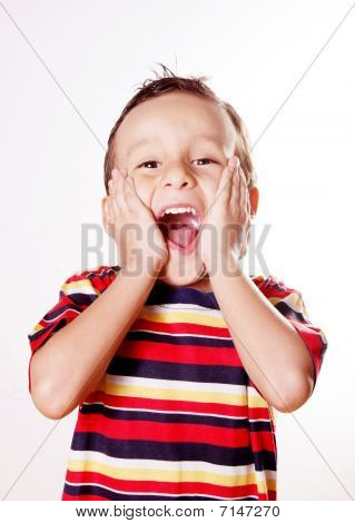 Child expressing surprise and happiness with his hands in his face stock photo