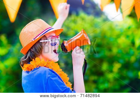 Happy Dutch boy football fan cheering and supporting soccer team of Netherlands during championship celebrating sports victory screaming Hup Holland in a megaphone stock photo