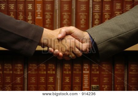 a handshake between two people with law books stock photo