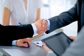 Business individuals shaking hands, completing up a meeting
