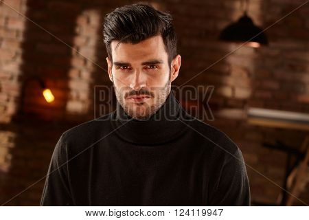 Portrait of handsome bristly man, looking at camera in black turtleneck. stock photo