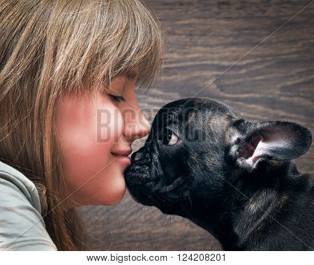 Kiss the girl and the dog. The dog is black, funny. French bulldog puppy. Love, man\'s relationship and Dogs