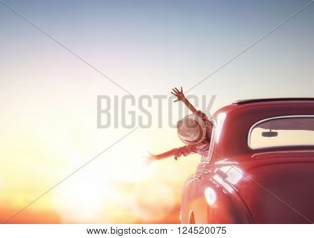 Toward adventure! Girl relaxing and enjoying road trip. Happy girl rides into the sunset in vintage