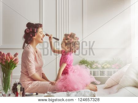 Happy loving family. Mother and daughter are doing hair and having fun. Mother and daughter doing yo