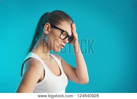 Young female having hangover or vertigo. Studio portrait over blue background. Concept of pain, symptom and health care. stock photo
