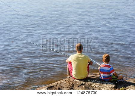Father and son lake fishing together. They\'re using telescopic fishing rods fishing line floats and baited fishing hooks. Man has tattoos.