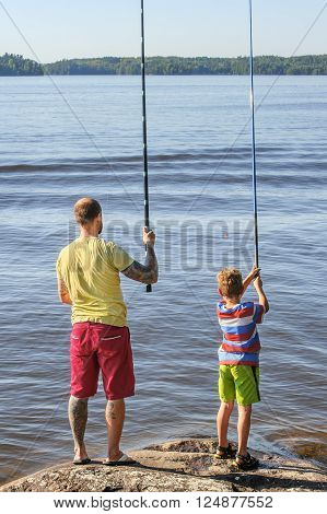 Father and son lake fishing together. They're using telescopic fishing rods, fishing line, floats, and baited fishing hooks. Man has tattoos. stock photo