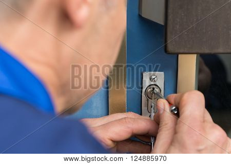 Close-up Of Male Lockpicker Hand Fixing Door Handle At Home ** Note: Shallow depth of field stock photo