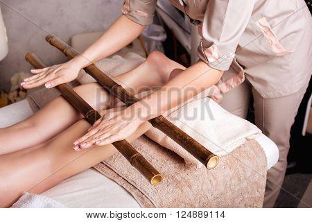 Massage of human foot in spa salon with bamboo sticks.\\ Closeup of legs Caucasian woman having a massage spa salon