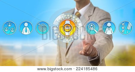 Unrecognizable recruitment agent is accessing social updates via smartwatch on the go. Information technology concept for wearable tech devices, professional productivity and last mile connectivity. stock photo