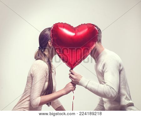 Valentine Couple. Beauty Girl and her Handsome Boyfriend holding heart shaped air balloon and kissin