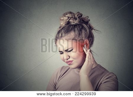 Tinnitus. Closeup up side profile sick female having ear pain touching her painful head colored in red isolated on gray background stock photo