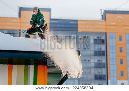 Snow cleaning. Team of male workers clean roof of building from snow with shovels in securing belts of mantra. stock photo