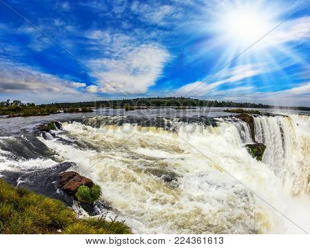 The Garganta del Diablo/ Devil's Throat is the most grandiose part of the Iguazu Falls on the Parana River. The autumn sun shines through the clouds. Concept of active and extreme tourism  stock photo