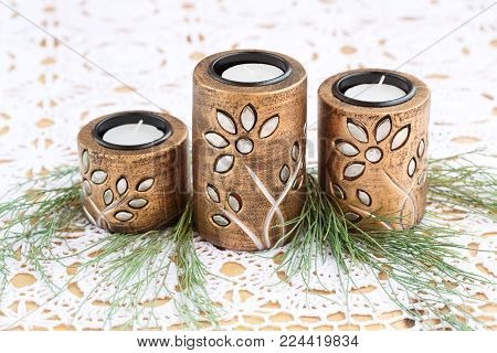 Three brown ancient style candle nests and green leaves on cloth background. stock photo