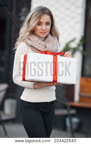 Pretty girl with long blonde hair,standing alone in the open air,holding a Christmas gift. Christmas woman with gift box.Cute young blonde in a white winter sweater with a red gift box, Christmas, New year, Valentine's Day gift stock photo