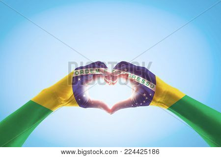 Brazil flag on people hands in heart shape for labor day and national holiday celebration isolated on blue sky background stock photo