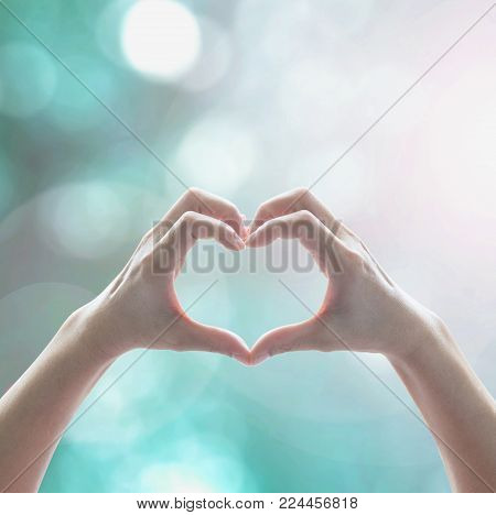 Healthy human hand in heart shape showing love friendship on blurred abstract cool blue green sky color bokeh background: Global eco environment CSR natural resource awareness/ concept/ campaign/ idea