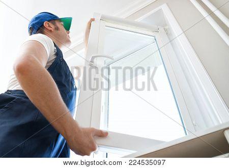 Professional handyman in uniform installing window at home.