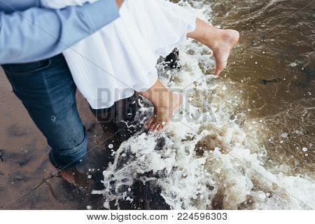 a man and a woman stand barefoot on the wet sand, their gogi is washed by water with foam and sprays. girl in white dress hanging down to water stock photo