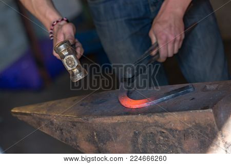 closeup on farrier making a traditional horseshoe on a forge stock photo