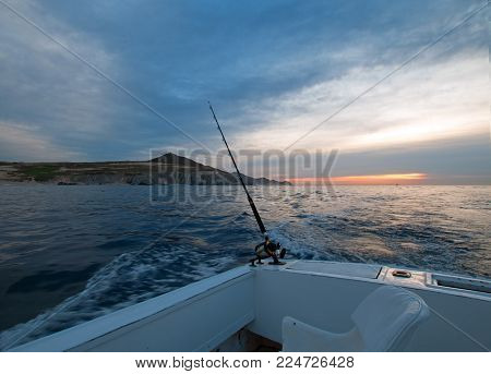 Sunrise view of fishing rod on charter fishing boat on the Pacific side of Cabo San Lucas in Baja California Mexico BCS stock photo