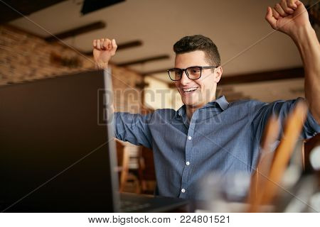 Handsome businessman with laptop having his arms with fists raised, celebrating success. Happy freelancer hipster in glasses finished work on project. Man won a lot of money in lottery prize. Business theme.