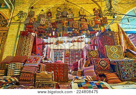 The old carpet stall with kilims and rugs for each taste - knotted-pile Persian carpets, woven nomadic tribal rugs, handmade or machine made, woolen or cotton, everything can be found in Vakil Bazaar, Shiraz, Iran. stock photo