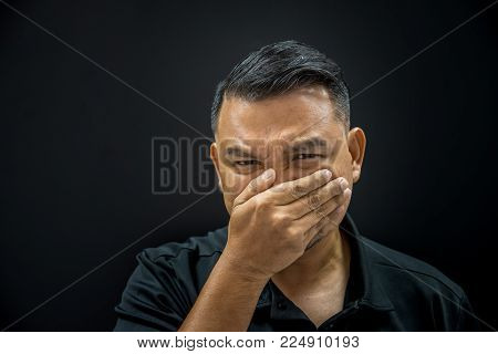 Asian man 40s have a short hair in black polo shirt make gestures off their nose and mouth to prevent unpleasant smell from the pollution or stench smell on black background dark style stock photo