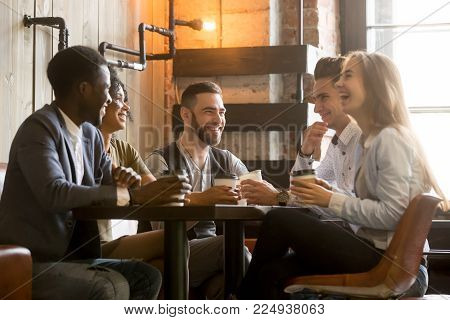 Multiracial friends having fun and laughing drinking coffee in coffeehouse, diverse young people talking joking sitting together at cafe table, multi ethnic millennials spending time in coffee shop