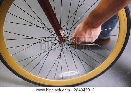 Theme repair bikes. Close-up of a Caucasian man's hand use a hand tool Bike Tools Hub Cone Wrenc to adjust and install Quick Releases and Thru Axles on a red bicycle. stock photo