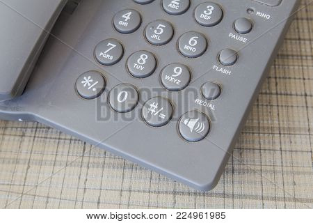 old and dirty grey telephone on the tablecloth of desk stock photo