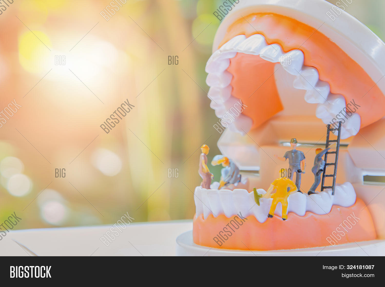 Miniature Worker People Or Small Figure Cleaning White Tooth Model As Medical And Healthcare Concept