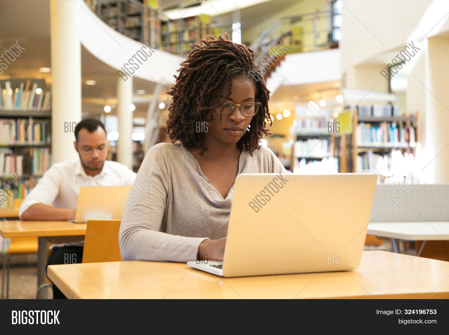 Serious African American Student Working On Research Paper In Library. People Sitting At Desks And U