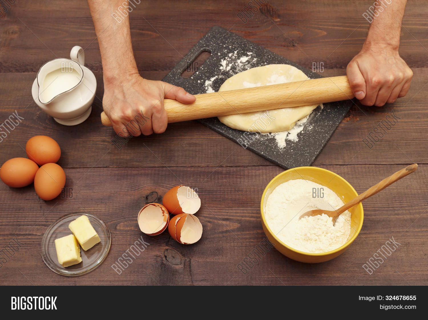 Baker Rolling Dough With Rolling Pin On The Board On A Rustic Table.