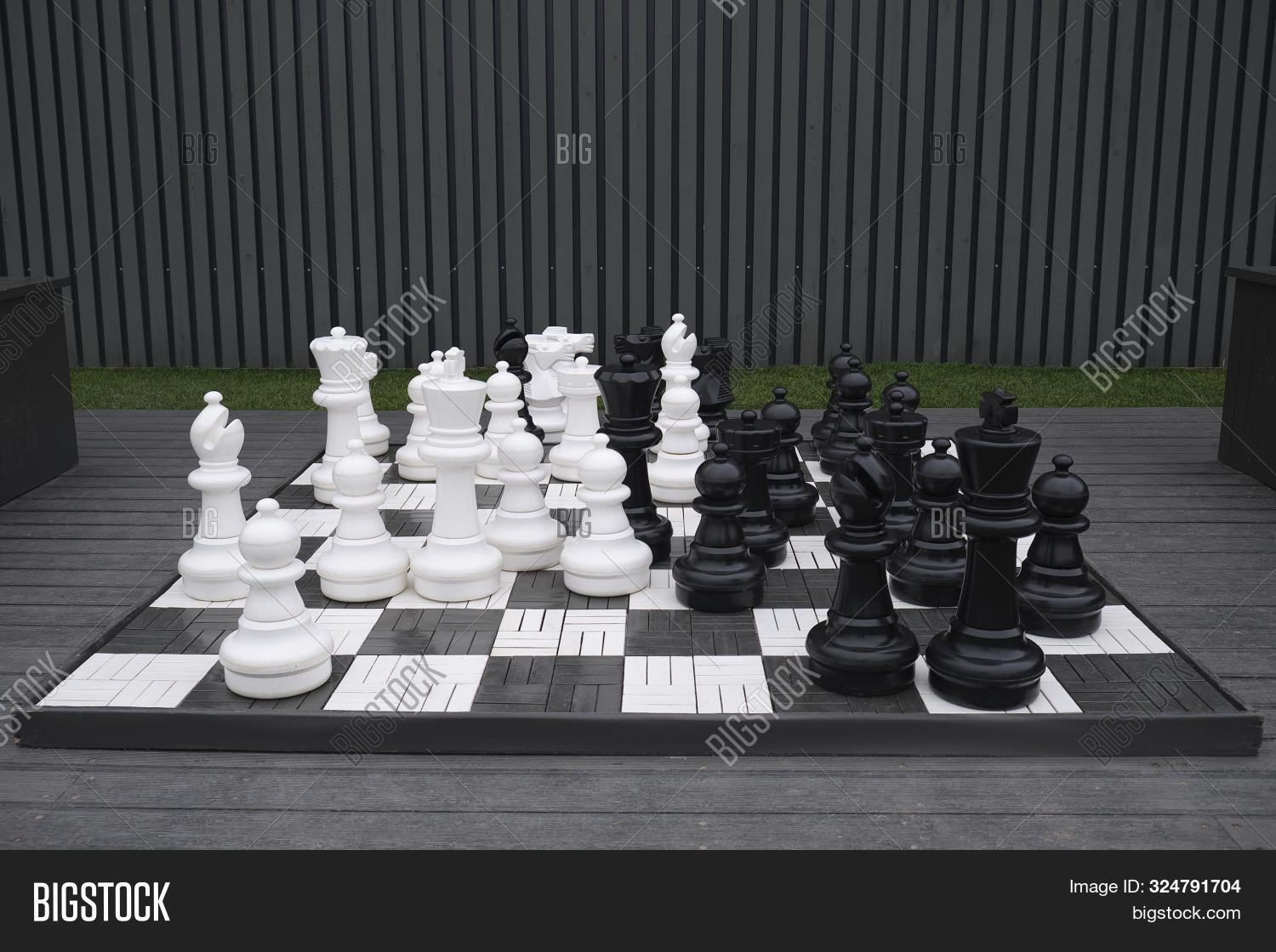 background,battle,big,bishop,black,board,brainstorm,checkmate,chess,chessboard,chessmen,close,closeup,competition,competitive,concept,develop,field,first,game,garden,giant,group,hand,huge,intelligence,king,large,leisure,lifestyle,move,objects,outdoor,outside,park,pawn,pieces,plastic,queen,rook,set,sport,strategic,strategy,team,thinking,victory,white,win