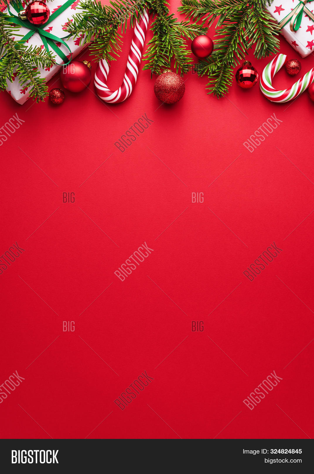 Red background. Copy space for Christmas creep. Border of fir branches, gifts, Christmas balls and candy cane